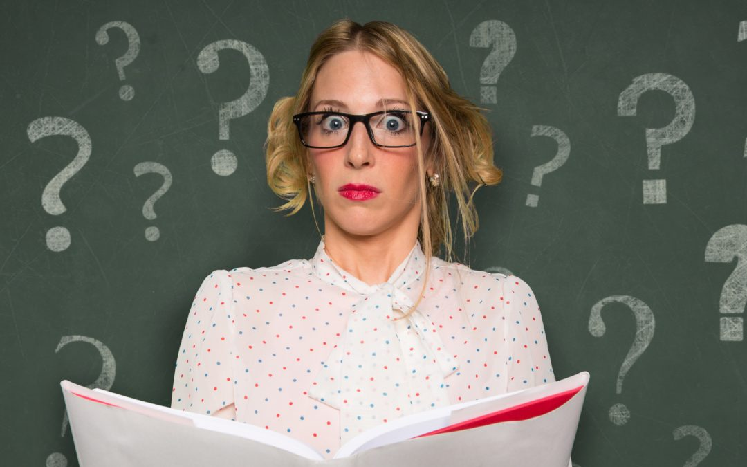Perplexed businesswoman holding a book in front of a chalkboard with question marks on it