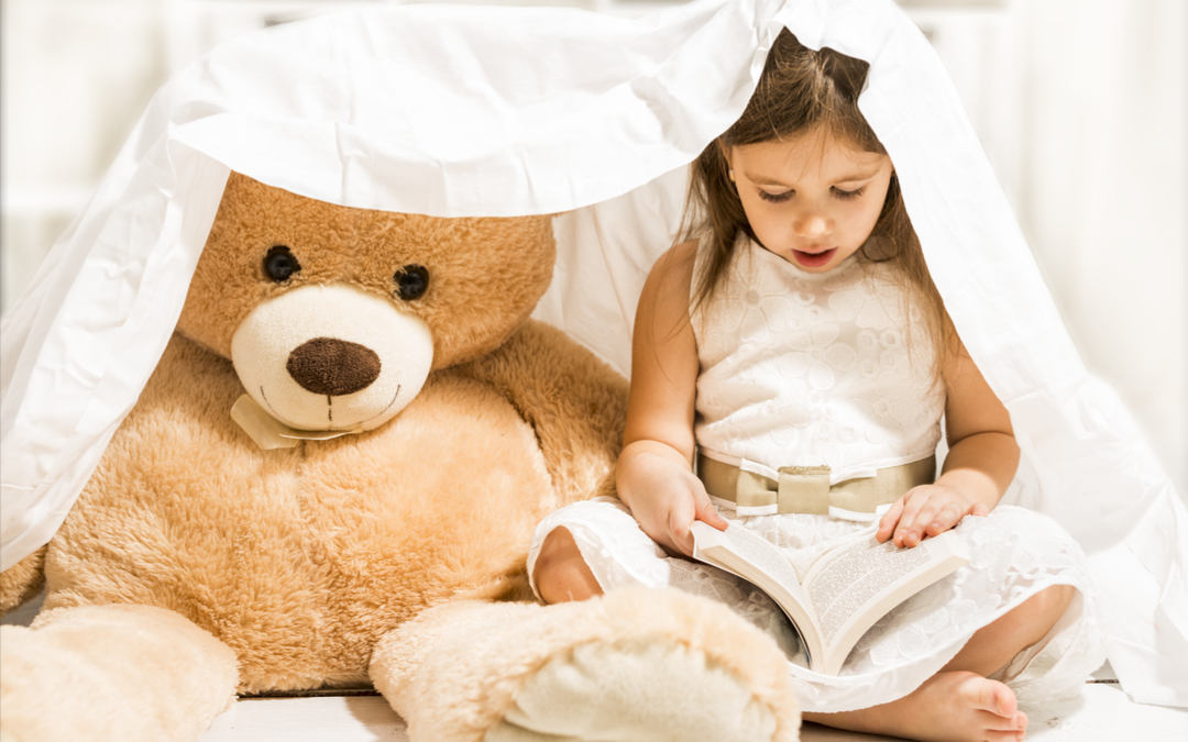 Little girl storytelling to a bear